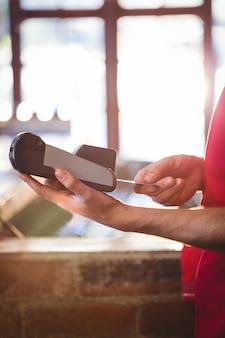 Cameriere che inserisce la carta di credito del cliente nella macchina della carta di credito