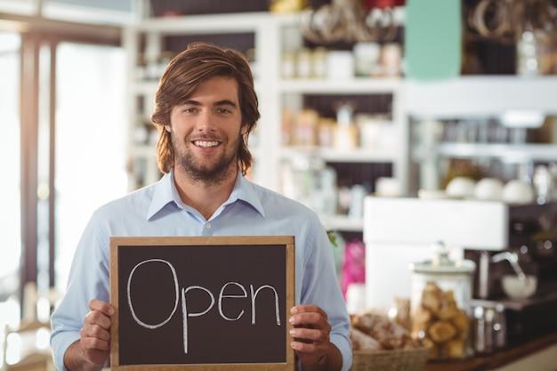 Cameriere che mostra lavagna con segno aperto