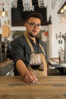 Cameriere che offre una tazza di vino in un pub