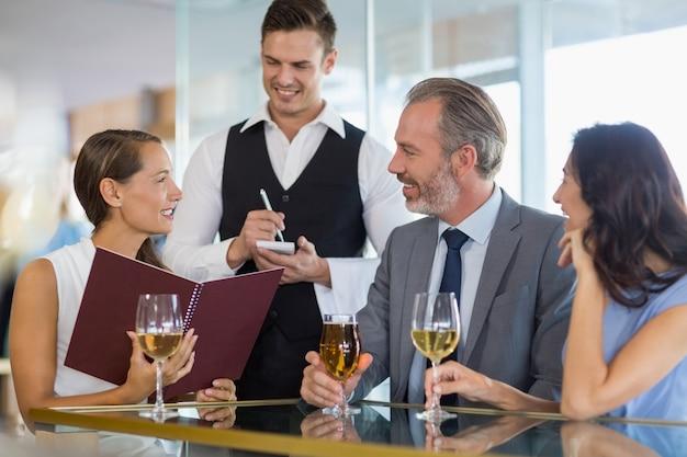 Cameriere che prende l'ordine da un uomo d'affari e dai suoi colleghi