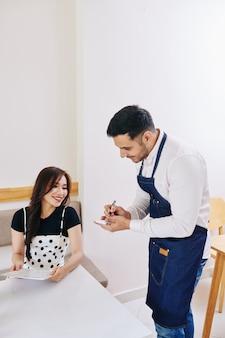 Cameriere che prende l'ordine dall'ospite