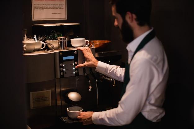 Cameriere che produce tazza di caffè dalla macchina del caffè espresso