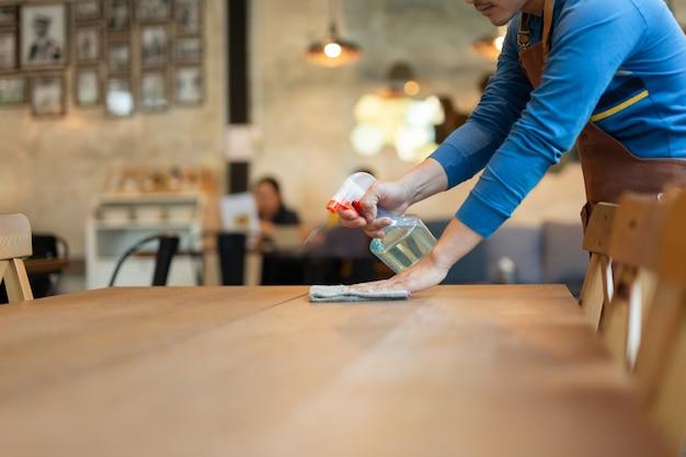Cameriere che pulisce un tavolo