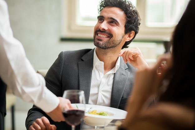 Cameriere che serve cibo a una coppia