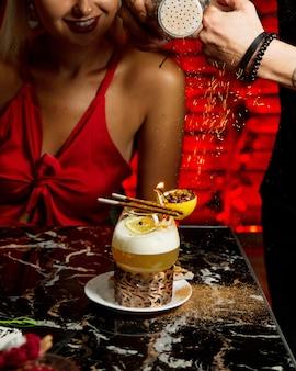 Cameriere che serve donna con un bicchiere di cocktail guarnito con molletta in fiamme