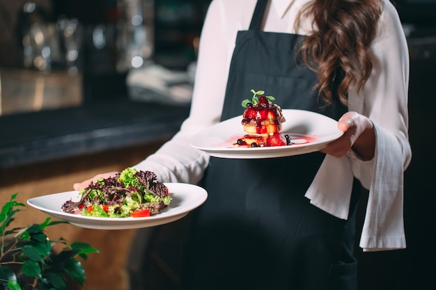 Cameriere che serve in movimento in servizio nel ristorante. il cameriere porta i piatti.