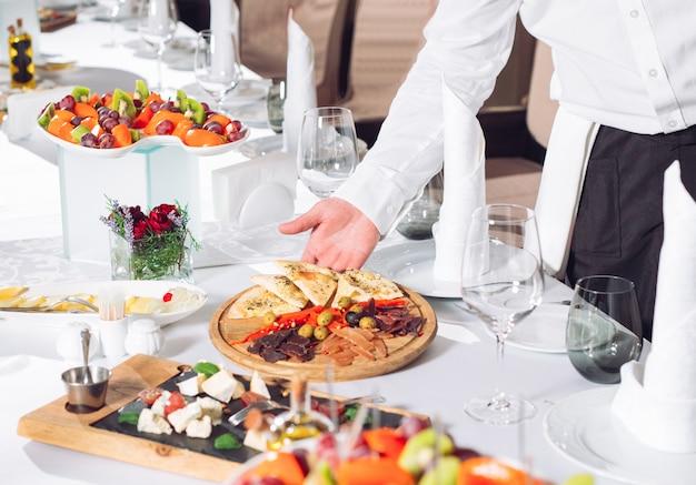 Cameriere che serve tavolo nel ristorante preparando a ricevere gli ospiti.