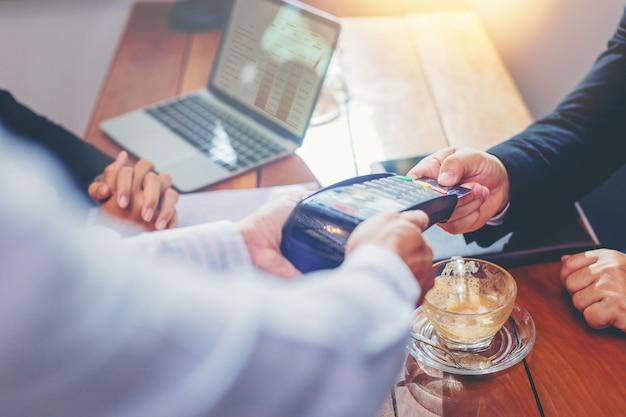 Cameriere che tiene lettore di carte di credito per uomo d'affari pagando il loro ordine