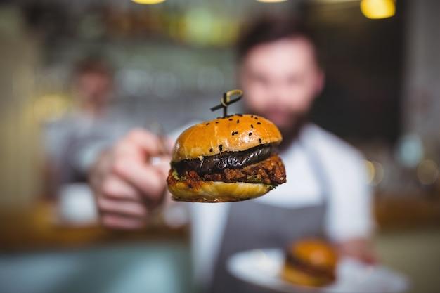 Cameriere che tiene un hamburger con tong