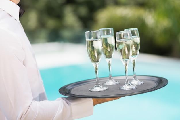 Cameriere che trasporta flute di champagne sul vassoio