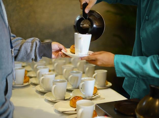 Cameriere che versa il caffè o il tè caldo nella tazza bianca e serve il piatto da forno per la pausa caffè alla festa
