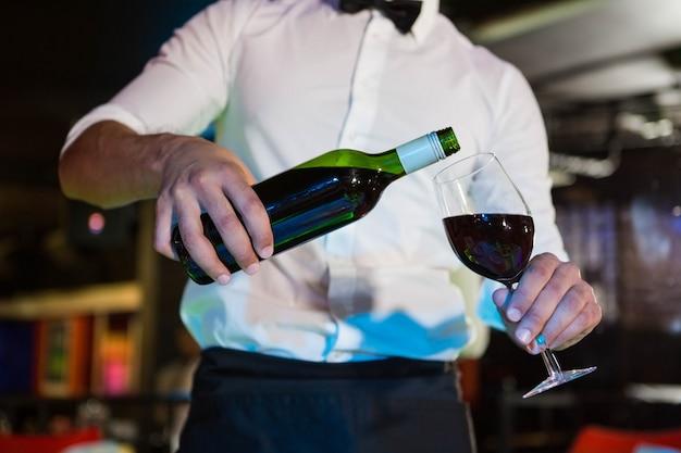 Cameriere che versa vino in un bicchiere nel bar