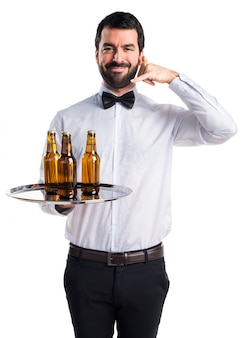Cameriere con bottiglie di birra sul vassoio facendo il gesto del telefono