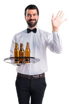 Cameriere con bottiglie di birra sul vassoio saluto