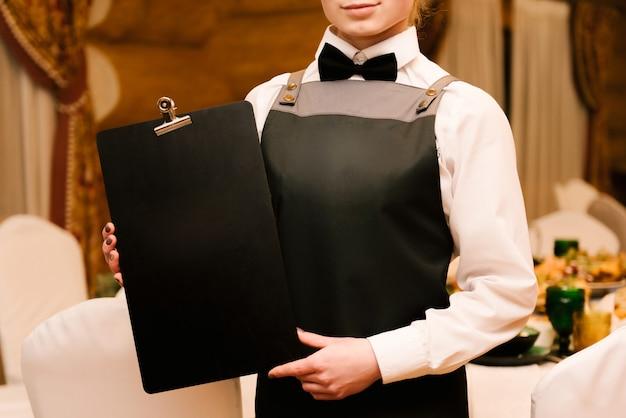 Cameriere con un menu nero tra le mani, copia spazio