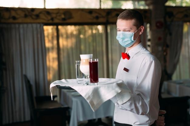 Cameriere dall'aspetto europeo in una maschera medica serve caffè latte.
