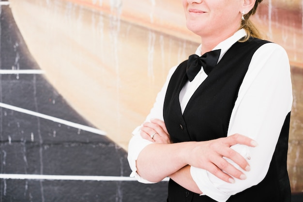 Cameriere di smiley che si tiene per mano e che aspetta per servire