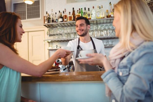 Cameriere felice che serve caffè al cliente presso la caffetteria