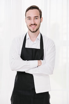 Cameriere felice in piedi con le mani incrociate
