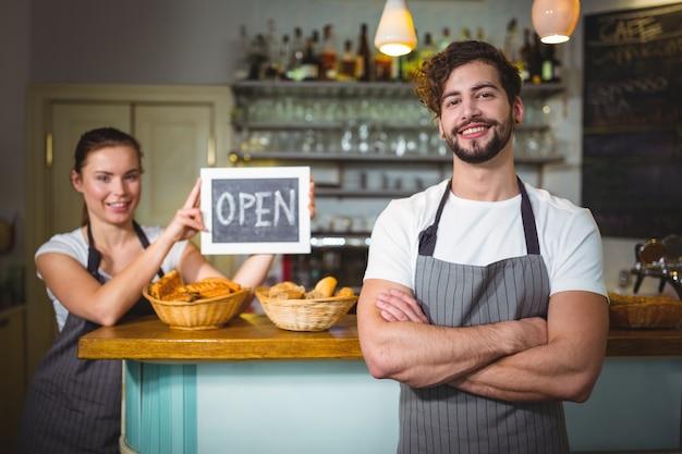 Cameriere in piedi con le braccia incrociate al contatore nel cafã ©