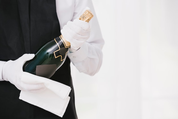 Cameriere in uniforme che presenta champagne