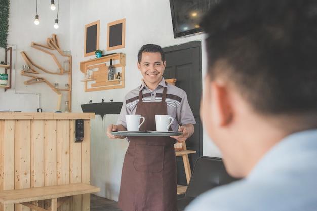 Cameriere maschio che consegna caffè al suo cliente