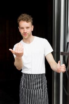 Cameriere maschio con grembiule vi invita all'interno della caffetteria
