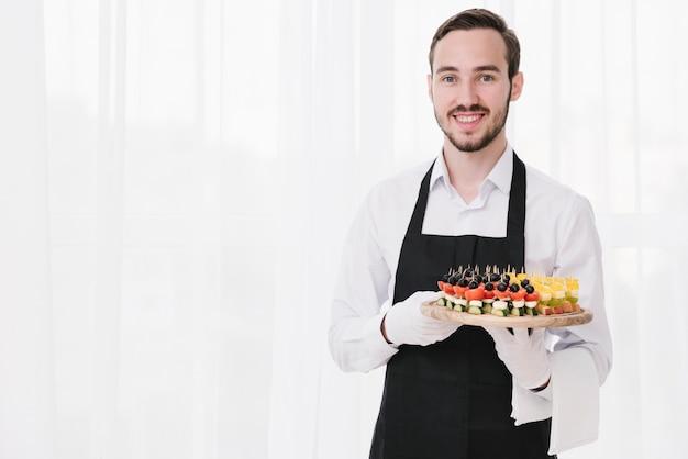 Cameriere professionista che presenta stuzzichini