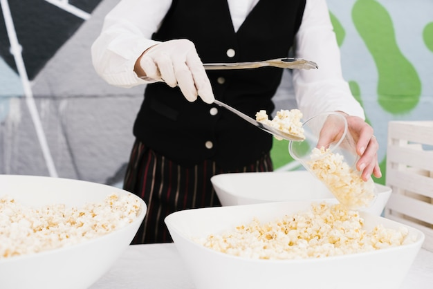 Cameriere riempiendo una tazza di popcorn con le tenaglie