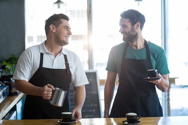Cameriere sorridente che interagisce mentre producendo tazza di caffè al contatore