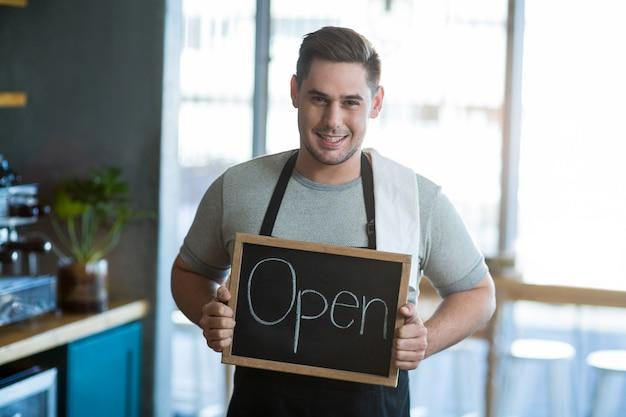 Cameriere sorridente che mostra ardesia con il segno aperto