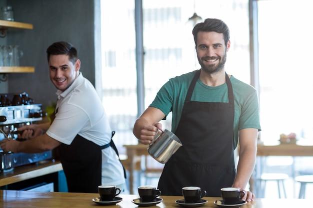 Cameriere sorridente che produce tazza di caffè al contatore in caffè