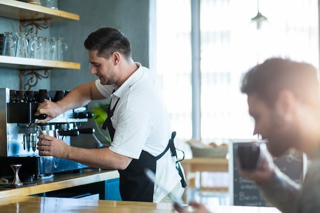 Cameriere sorridente che produce tazza di caffè