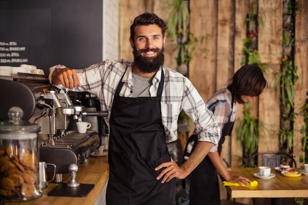 Cameriere sorridente che sta nella cucina al caffè
