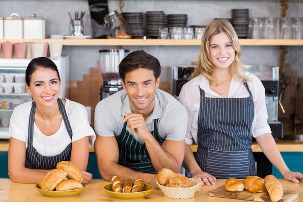 Cameriere sorridente e due cameriere appoggiato al bancone