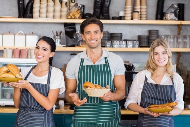 Cameriere sorridente e due cameriere che tengono il piatto di panini