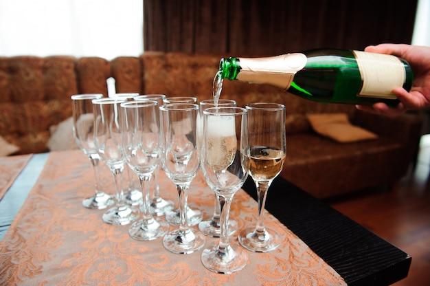 Cameriere versa champagne in bicchieri, evento di lusso.