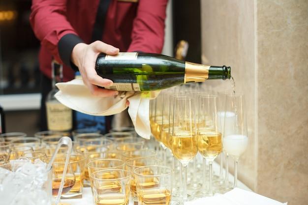 Cameriere versando champagne in un bicchiere da flauto