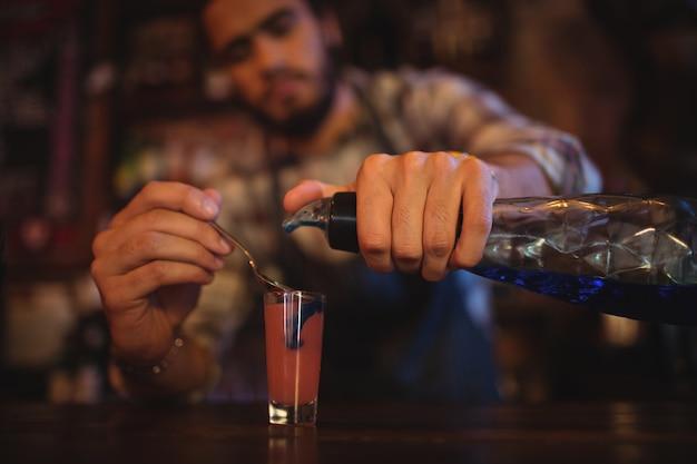 Cameriere versando cocktail drink in bicchierini al bancone