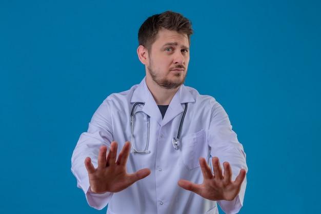 Camice d'uso e stetoscopio di medico del giovane che fanno il fanale di arresto, gesto della difesa sopra fondo blu isolato