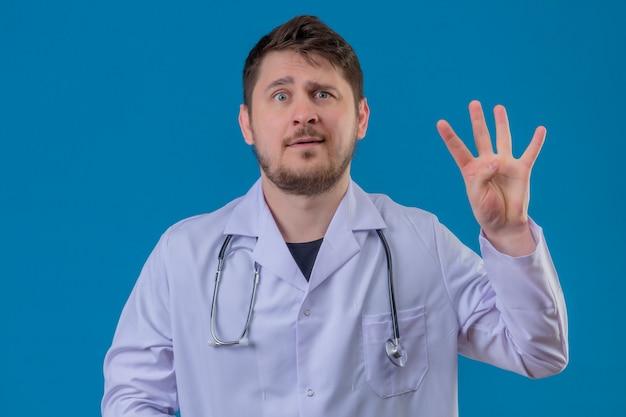 Camice d'uso e stetoscopio di medico del giovane con il sorriso che mostra numero tre con le dita sopra fondo blu isolato