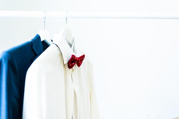 Camicia bianca classica da uomo con un papillon rosso e un abito su una gruccia