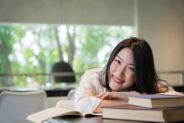 Camicia bianca d'uso del bello studente che riposa mentre libri di lettura sulla tavola in biblioteca