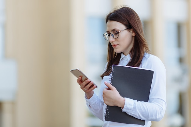Camicia bianca d'uso della giovane donna di affari del ritratto facendo uso delle porte dello smartphone.
