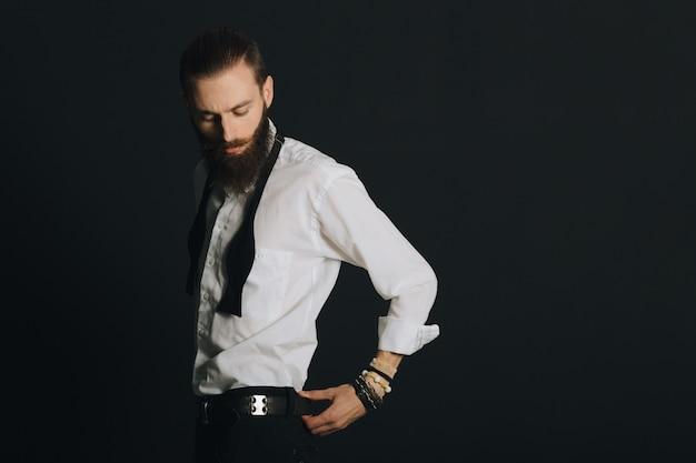 Camicia bianca dell'uomo barbuto di stile hipster in studio su fondo nero