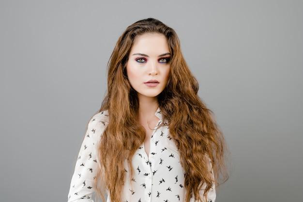 Camicia e jeans weraing della donna abbastanza emozionale isolati sopra la parete grigia