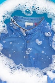 Camicia jean imbevuta di polvere detergente dissoluzione dell'acqua. concetto di lavanderia