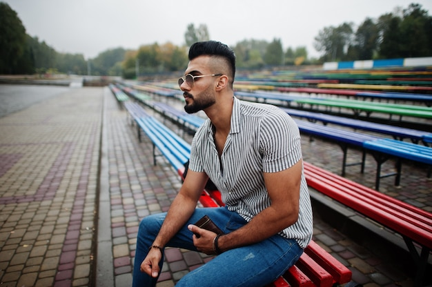 Camicia, jeans ed occhiali da sole d'uso alla moda dell'uomo barbuto alto che si siedono sulla fila di panche colorata