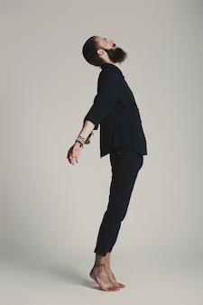 Camicia nera dell'uomo barbuto di stile dei pantaloni a vita bassa in studio sopra fondo bianco