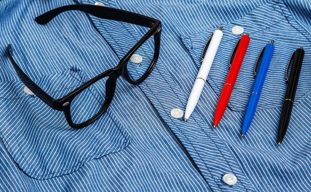 Camicia, occhiali da vista e penne colorate